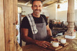 canvas print picture - Male barista serving coffee to customers