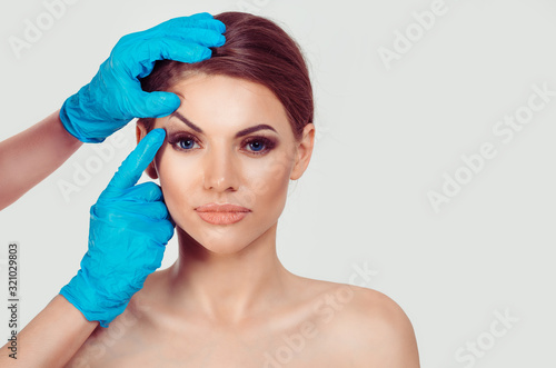 Obraz Upper eyelid blepharoplasty. Beautiful middle age woman getting ready for eyelid lift plastic surgery doctor hands in blue gloves point fingers to her eye on white. Beauty, people and health concept - fototapety do salonu