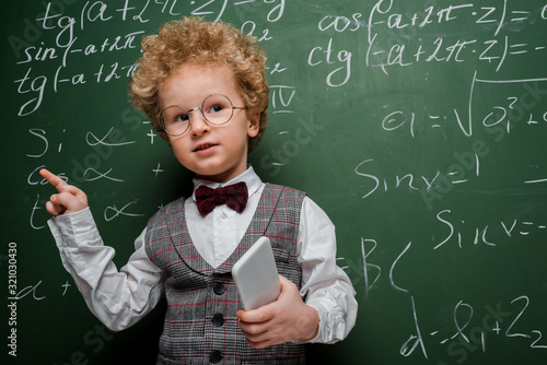 smart child in suit and bow tie holding smartphone and pointing with finger near chalkboard with mathematical formulas