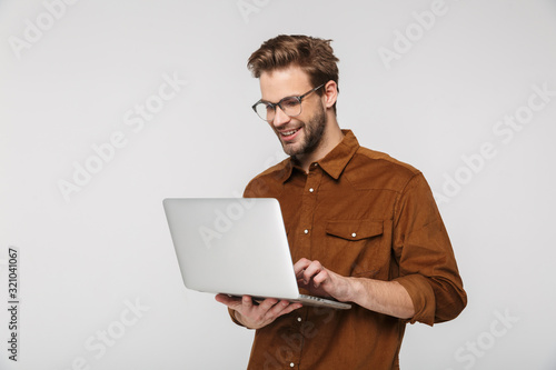 Obraz Portrait of cheerful young man using laptop and smiling - fototapety do salonu