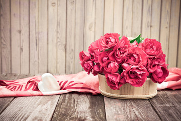 Flowers. Bouquet of red roses with Heart of marble on wooden table. Vintage V...
