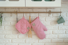 Kitchen Glove, Potholder, Oven Protection Are Hanging Over White Brick Wall. Safety Cooking Concept. Copy Space