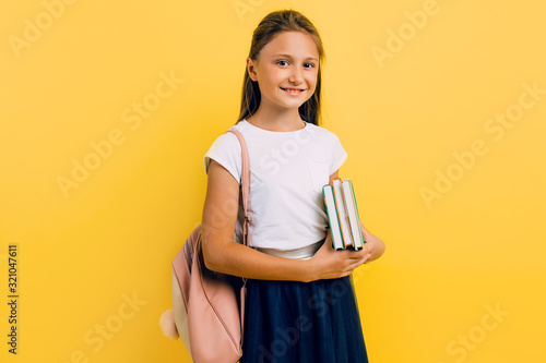 Obraz A teenager with a backpack and books. Stylish beautiful schoolgirl posing on a yellow background - fototapety do salonu