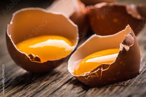 Fotomural Broken chicken eggs with yolk on wooden table