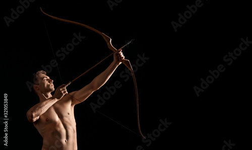 Athletic archer shooting with bow. Wallpaper Mural