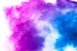 Leinwandbild Motiv Explosion of blue pink colored powder isolated on white background.Pink blue dust splash.