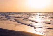 Sunrise On The Beach. Gentle Waves Hit The Shore As The Sun Rises Over The Sea. Travel And Tourism Landscape Background With Copy Space.