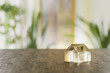 A model of a small house in frosted glass on a wooden table. Copy space available.
