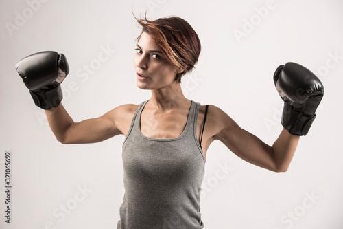 Photo donna  con i guantoni da boxe isolata su sfondo grigio chiaro
