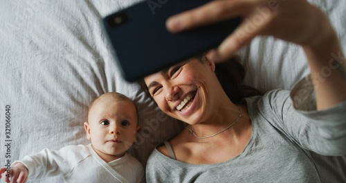 Obraz Authentic close up of neo mother and her newborn baby making a selfie or video call to father or relatives in a bed. Concept of technology, new generation,family, connection, parenthood, authenticity - fototapety do salonu