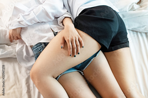 Leinwand Poster Closeup legs of Asian couple woman embracing together on bed,Lesbian lovers,roma