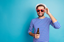 Photo Of Nice Traveler Guy Drink Beer Bottle All Inclusive Exotic Resort Good Mood Summer Holidays Wear Sun Specs Striped Sailor Shirt Cap Isolated Blue Color Background