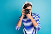 Photo Of Attractive Guy Photographer Hold Professional Digital Lens Camera Traveler Make View Pictures Wear Striped Sailor Shirt Vest White Cap Isolated Blue Color Background