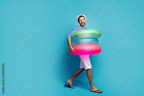 fototapeta na ścianę Full length profile photo of funky guy tourist walking seaside inside three colorful rubber lifebuoys swimmer wear striped sailor shirt cap shorts flip flops isolated blue color background