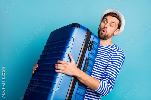 fototapeta na drzwi i meble Photo of handsome guy traveler hold big suitcase plane flight weight allowance too heavy bag feel back pain wear striped sailor shirt vest panama isolated blue color background