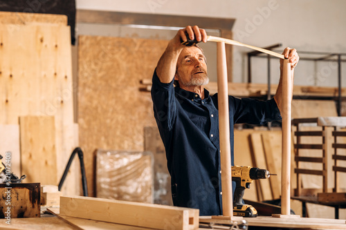 Carpenter measures the width between the legs of a table in a workshop Slika na platnu