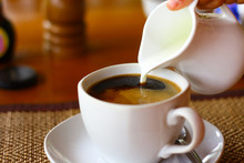 Hand Pouring Milk To Coffee Cup On Wood Table Background