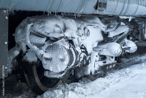 Photo ice covered bogie of a railway passenger carriage on rails in winter