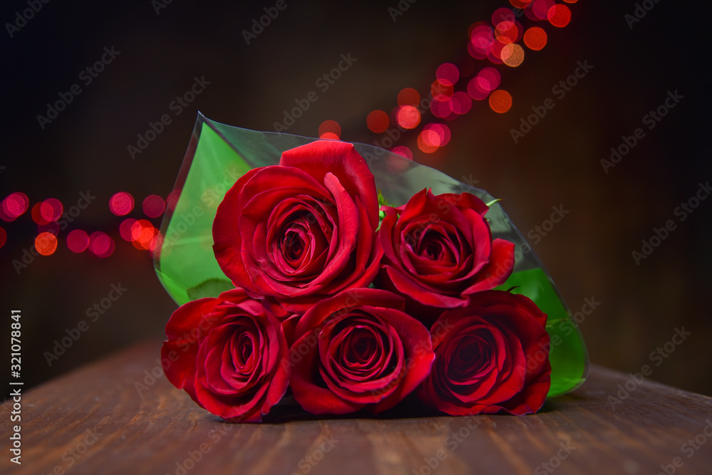 Fototapeta Beautiful Red Roses Piled in Bouquet Wrapped in Green Paper with Red Bokeh Lights