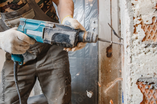 Obraz na plátně Builder worker pneumatic hammer drills hole in concrete brick wall with diamond