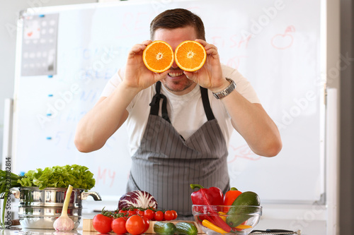 Fototapeta Chef Vlogger Showing Comic Orange Citrus Eye. Vegan Man with Cut Halves in Kitchen. Healthy and Fresh Juicy Fruit Ingredient. Fresh Tomatoes, Cabbage and Avocado for Lunch Looking at Camera Shoot obraz
