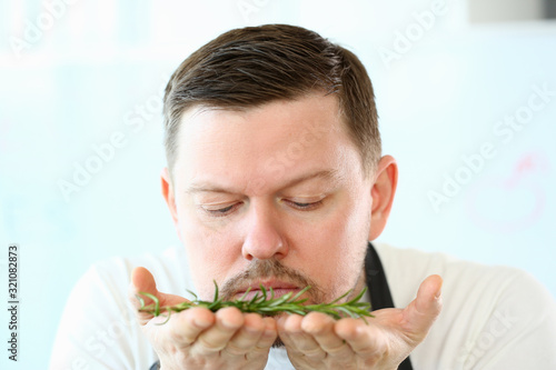 Fototapeta Blogger Beard Chef Smelling Aromatic Rosemary Herb. Man Holding Green Herbal Plant on Hands. Cook with Greens Ingredient for Vegetarian Food. Natural Culinary Spice Blog Head and Shoulders Photography obraz