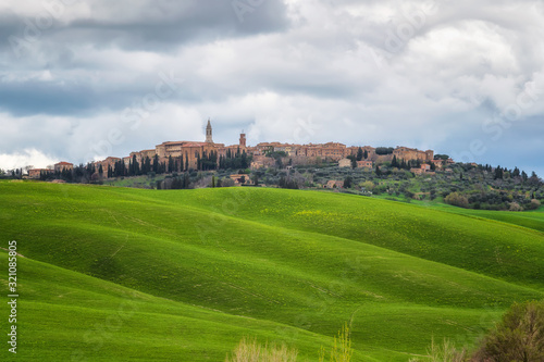 Amazing spring landscape with green rolling hills and old town of Pienza in the Wallpaper Mural
