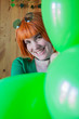 canvas print picture - Attractive and sexy redhead woman with green and golden sunglasses looking straight ahead with green balloons celebrating St. Patrick's Day with a wooden background