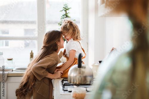 Obraz Two sisters play in a bright, stylish kitchen. Beautiful interior. - fototapety do salonu