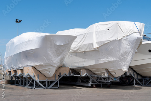 Valokuva power boat parked covered white protective plastic film New boats in cover casin