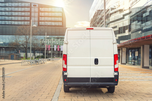 obraz dibond Small cargo delivery van driving in european city central district. Medium lorry minivan courier vehicle deliver package at residential office building in downtown area. Commercial shipping logistics