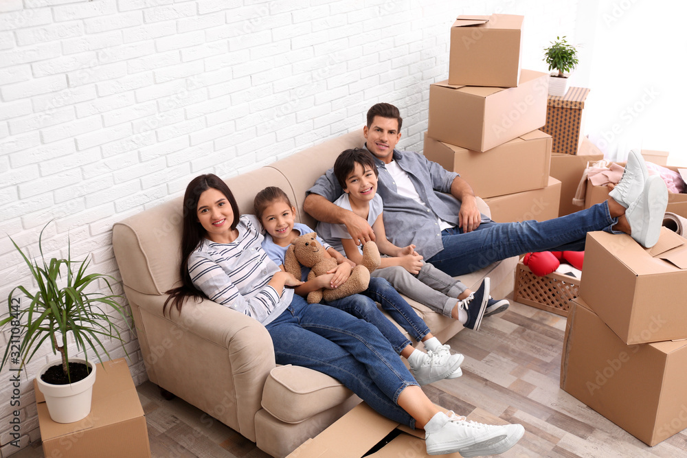 Fototapeta Happy family resting in room with cardboard boxes on moving day
