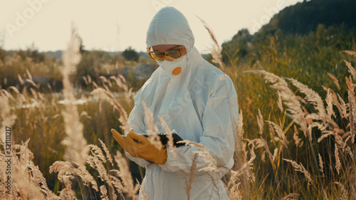 Ecological specialist in white protective costume staying at radioactive swamp in polluted landscape measuring contamination Canvas-taulu