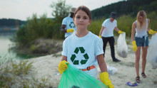 Porrtrait Of Little Cute Cheerful Girl Cleaning The Sandy Beach From Garbage Smiling Of Joy Having Good Time Outdoor. Young Volunteer Team On Eco-friendly Movement.