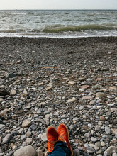 Feet In Red Boots On Seaside. View On Seascape From Rocky Beach. Travel Concept. Man Or Woman In Hiking Shoes Is Relaxing Outdoors.