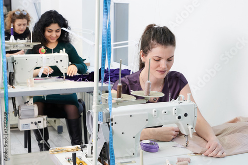 Young tailors sew clothes on sewing machine in atelier studio Canvas Print