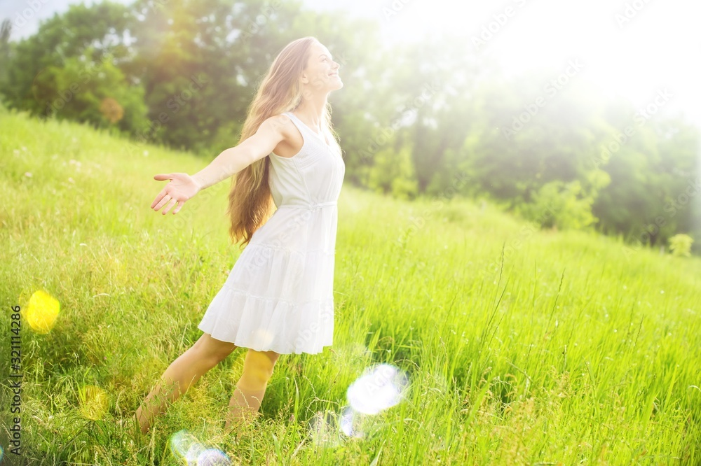 Fototapeta Young relaxed woman in the green field