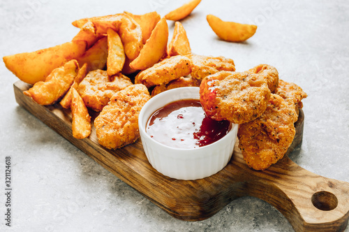 Fototapeta Serving on a wooden board crumbed fried nuggets with fried potato and a small bowl of sauce or dip on a stone background. Top view. Copy space obraz