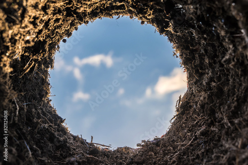 Erdloch mit der Sicht aus dem Loch Richtung Himmel als besonderes Symbol zum Thema Einpflanzen, Mauseloch oder Maulwurfhügel