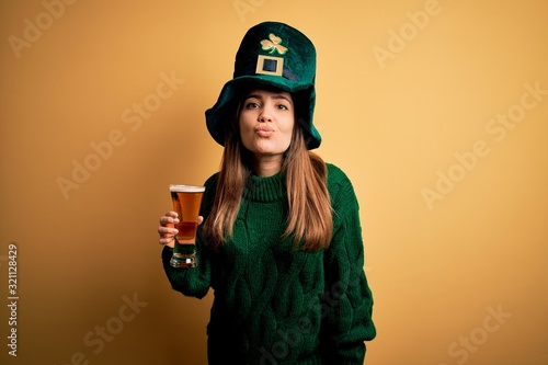 Young beautiful woman wearing green hat drinking glass of beer on saint patricks day looking at the camera blowing a kiss on air being lovely and sexy. Love expression.