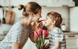 Fototapeta Tulipany - happy mother's day! child son gives flowers for  mother on holiday .