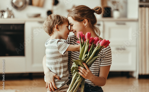 Obraz happy mother's day! child son gives flowers for  mother on holiday . - fototapety do salonu
