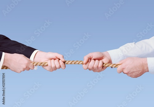 Photo Tug war, two businessman pulling a rope in opposite directions isolated on white