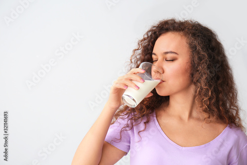 Valokuvatapetti Young African-American woman with milk on grey background