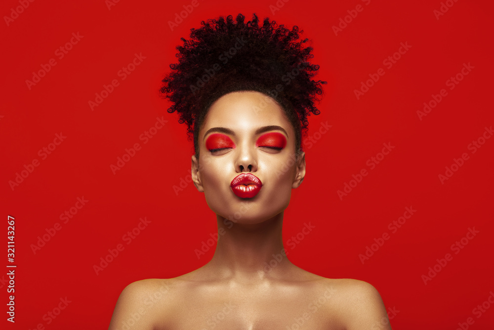 Fototapeta Kiss lips. Share love.Valentine Day. African makeup face. Satisfied Brunette young woman with afro hair style against colorful background.