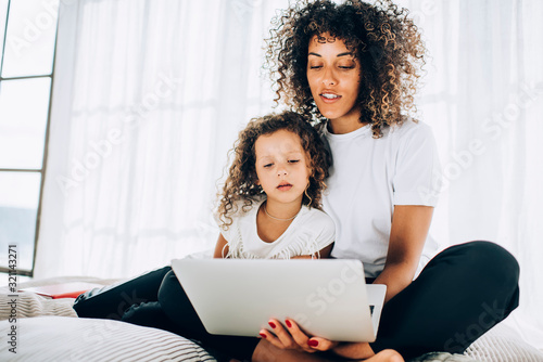 Caring mother surfing on laptop embracing curly haired daughter