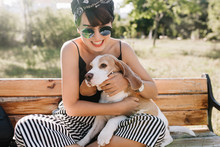 Close-up Outdoor Portrait Of Fascinating Laughing Girl Holding Beagle Puppy While Sitting On Bench. Pleased Young Woman In Sunglasses Playing With Dog In The Park.