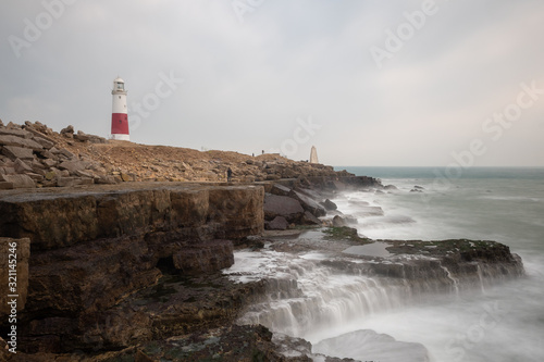 Fotografia Long exposure of the tide flowing over rocks on the beach at Portland Bill light