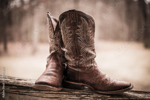 Photo Brown western style boots sitting on a fence in the country