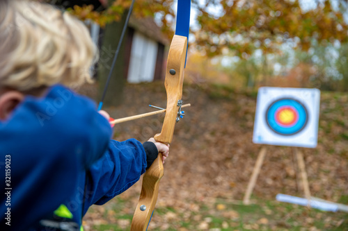 Children shot on target during a competition in archery in the forest Fototapete